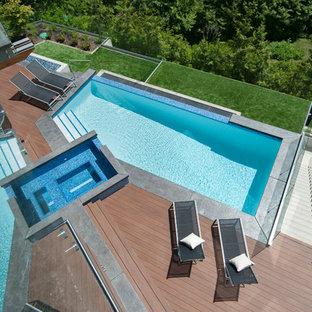 Esempio di una piscina a sfioro infinito minimal personalizzata dietro casa con una vasca idromassaggio e pedane