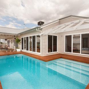"""Immagine di una piscina fuori terra stile marino a """"L"""" di medie dimensioni e sul tetto con pedane"""