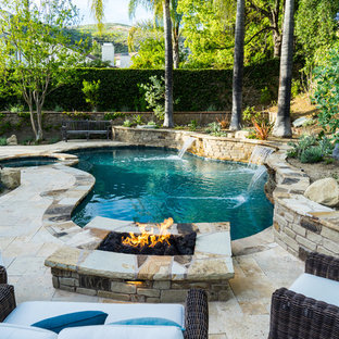 Inspiration for a rustic backyard stone and custom-shaped hot tub remodel in Los Angeles