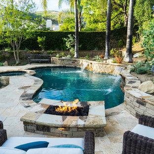 Ejemplo de piscinas y jacuzzis rústicos, a medida, en patio trasero, con adoquines de piedra natural