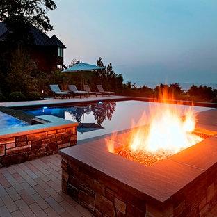 Immagine di una grande piscina monocorsia design rettangolare dietro casa con pavimentazioni in mattoni