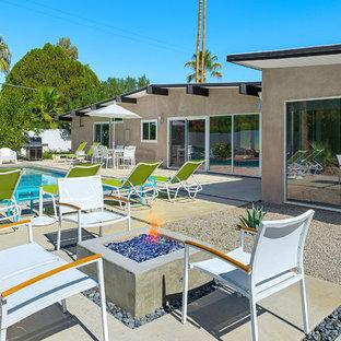 Imagen de piscina alargada, vintage, grande, rectangular, en patio trasero, con losas de hormigón