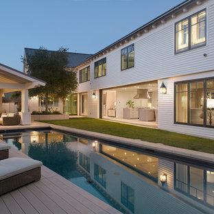 Esempio di una piscina classica rettangolare dietro casa con pedane e una dépendance a bordo piscina