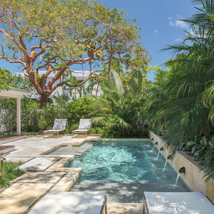 Example of a small island style backyard tile and custom-shaped lap pool fountain design in Miami
