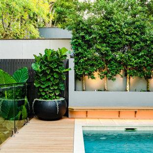 На фото: маленький прямоугольный бассейн на заднем дворе в современном стиле с настилом с