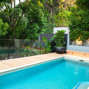 This is an example of a small tropical backyard rectangular pool in Brisbane with decking.
