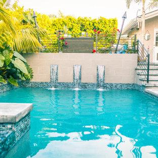 Ejemplo de piscina con fuente natural, actual, en forma de L, en patio trasero, con adoquines de hormigón