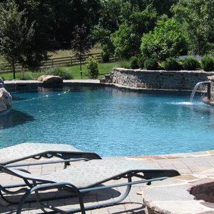 Ejemplo de piscina con fuente alargada, rústica, grande, a medida, en patio trasero, con suelo de baldosas