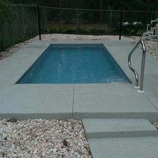 Foto de piscina pequeña, rectangular, en patio trasero, con losas de hormigón