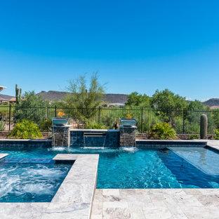 Réalisation d'une piscine arrière sud-ouest américain en L de taille moyenne avec des pavés en pierre naturelle et un point d'eau.