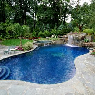 Immagine di una grande piscina tropicale personalizzata dietro casa con una vasca idromassaggio e pavimentazioni in pietra naturale