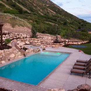 Foto de piscina con tobogán elevada, de estilo americano, de tamaño medio, rectangular, en patio trasero, con adoquines de hormigón