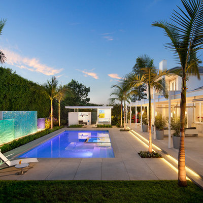 Example of a large trendy backyard rectangular and concrete paver lap pool design in Los Angeles