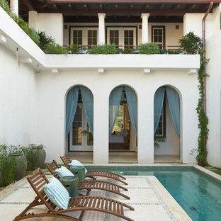 Design ideas for a mediterranean courtyard custom-shaped pool in Miami.