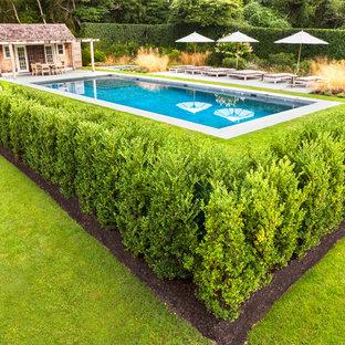 Foto de casa de la piscina y piscina actual, grande, rectangular, en patio lateral, con adoquines de hormigón