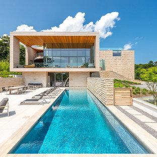 Imagen de piscina alargada, actual, rectangular, en patio lateral, con adoquines de piedra natural
