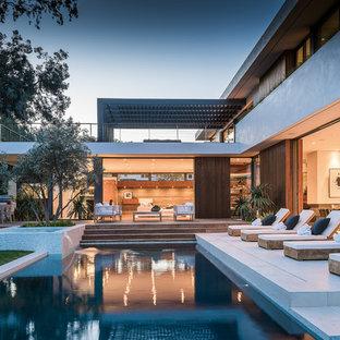 Ispirazione per una grande piscina moderna rettangolare dietro casa con fontane