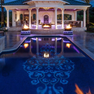 Example of a huge tuscan backyard custom-shaped infinity hot tub design in Tampa