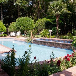 Imagen de piscina alargada, ecléctica, grande, a medida, en patio trasero, con adoquines de ladrillo