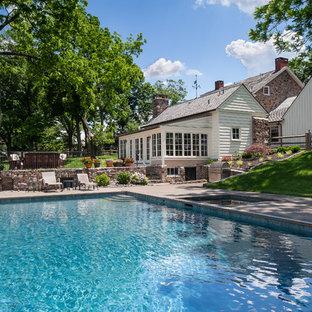 Ejemplo de piscina tradicional, grande, rectangular, en patio trasero, con granito descompuesto