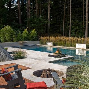 Idee per una grande piscina monocorsia contemporanea rettangolare dietro casa con una vasca idromassaggio e lastre di cemento