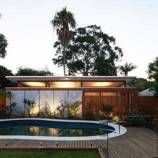 Modelo de piscina moderna, de tamaño medio, tipo riñón, en patio trasero, con entablado