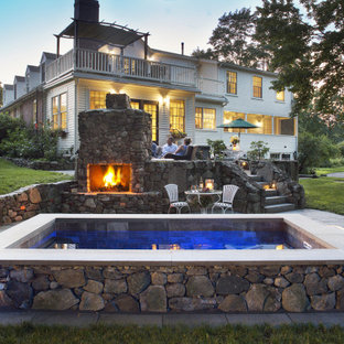 This is an example of a small country backyard rectangular natural pool in Boston with a hot tub and natural stone pavers.