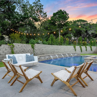 Inspiration for a country backyard l-shaped pool in Austin with a water feature and concrete slab.