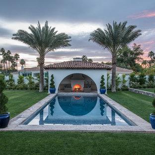 Ejemplo de casa de la piscina y piscina alargada, mediterránea, grande, rectangular, en patio trasero, con adoquines de piedra natural