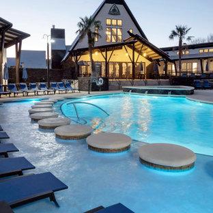 Immagine di una grande piscina country personalizzata in cortile con una vasca idromassaggio e lastre di cemento