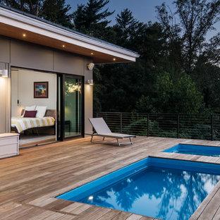 Exemple d'une piscine sur une terrasse en bois scandinave rectangle avec un bain bouillonnant.
