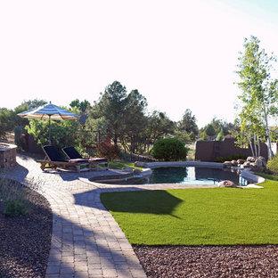 Ejemplo de piscina con fuente de estilo americano, grande, a medida, en patio trasero, con adoquines de ladrillo