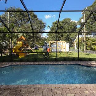 Foto de piscina natural, tradicional, de tamaño medio, a medida, en patio trasero, con adoquines de ladrillo