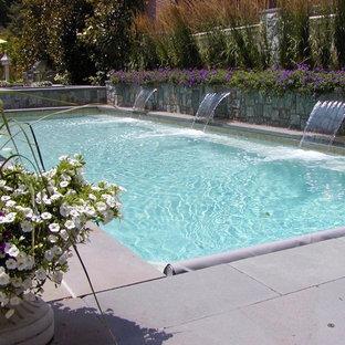 Modelo de piscinas y jacuzzis alargados, tradicionales, de tamaño medio, rectangulares, en patio trasero, con adoquines de hormigón