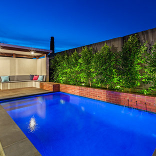 This is an example of a small contemporary backyard rectangular aboveground pool in Melbourne with a water feature.