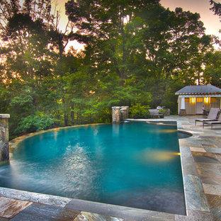 Ejemplo de piscina con fuente infinita, de estilo americano, grande, a medida, en patio trasero, con adoquines de piedra natural
