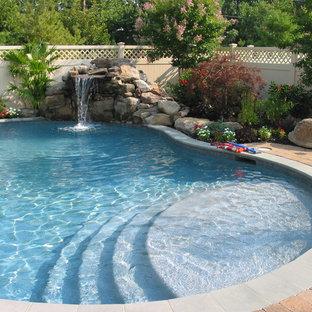 Diseño de piscina con fuente natural, tradicional, de tamaño medio, tipo riñón, en patio trasero, con adoquines de hormigón