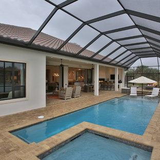 Ejemplo de piscina ecléctica, rectangular y interior, con adoquines de ladrillo