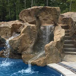 Foto di una grande piscina naturale tropicale dietro casa con un acquascivolo e pavimentazioni in pietra naturale