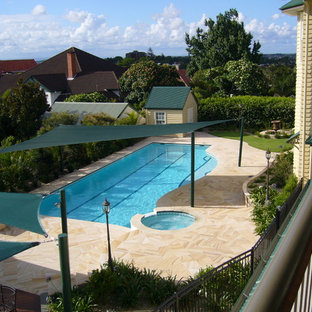 This is an example of a large contemporary backyard rectangular lap pool in Brisbane with natural stone pavers.