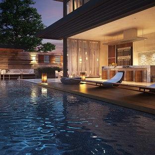 Diseño de piscina infinita, moderna, grande, rectangular, en patio trasero, con suelo de baldosas