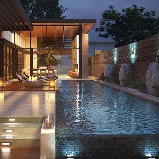 Ispirazione per una grande piscina a sfioro infinito moderna rettangolare dietro casa con piastrelle
