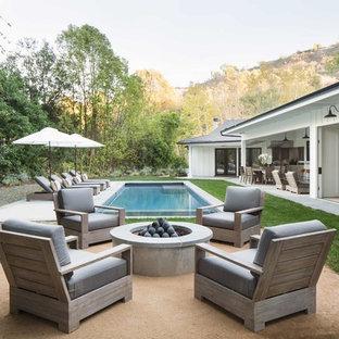 Ejemplo de piscina alargada, campestre, rectangular, en patio trasero, con adoquines de hormigón