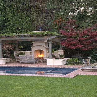 Modelo de piscina alargada, clásica, de tamaño medio, rectangular, en patio trasero, con adoquines de ladrillo