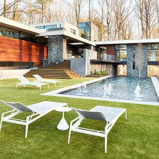 Modern inredning av en mycket stor rektangulär infinitypool på baksidan av huset, med en fontän och marksten i betong