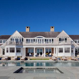 Réalisation d'une très grand piscine arrière victorienne rectangle avec un bain bouillonnant et des pavés en béton.