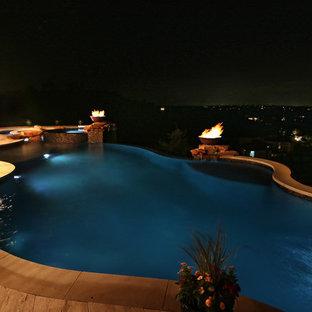 Ejemplo de piscina con tobogán infinita, mediterránea, extra grande, a medida, en patio trasero, con adoquines de piedra natural