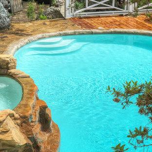 Imagen de piscina con tobogán natural, rural, pequeña, a medida, en patio trasero, con suelo de hormigón estampado