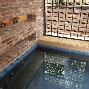 Ejemplo de piscina industrial, rectangular y interior, con adoquines de ladrillo