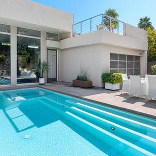 Foto de piscinas y jacuzzis alargados, modernos, de tamaño medio, rectangulares, en patio delantero, con losas de hormigón